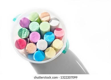 Pack of Jumbo Sidewalk Chalk, Assorted Colors in a Plastic Bucket on White Background with Shadow. Top View.