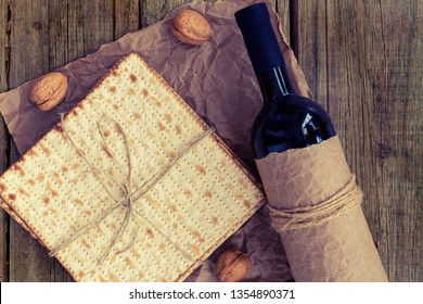 Pack of matzah or matza and a bottle of red kosher wine  on a rustic wood background