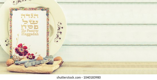 Pack of matzah or matza, Passover Haggadah and white passover seder plate on a vintage wood background with copy space.Hebrew text translation: The story of Passover