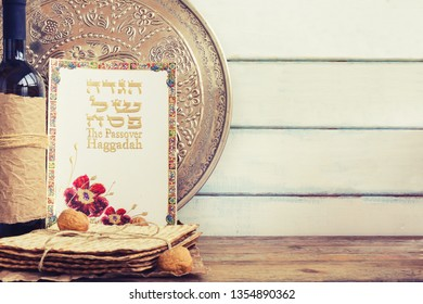 Pack of matzah or matza, Passover Haggadah and red kosher wine on a vintage wood background with copy space.Hebrew text translation: The story of Passover