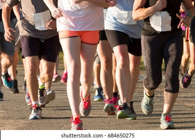 A pack of runners competing in a local five thousand meter race, both men and women together, on a sunny summer early evening