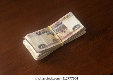 a pack of Russian money in denominations of five hundred roubles laid on the table and wrapped a rubber band