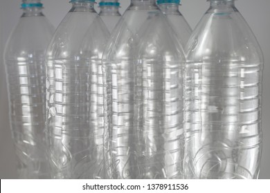 Pack of standing Bottles of a liter and a half of empty mineral water without lids just with the sealing ring on a white background. Reuse, Eco-Friendly, Environment, Conservation, Sustainable
