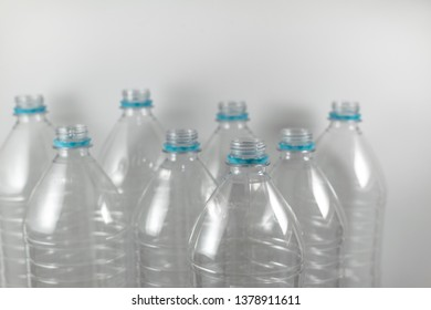 Pack of standing empty Bottles of mineral water without lids just with the sealing ring on a white background. Reuse, Eco-Friendly, Environment, Conservation, Sustainable concept