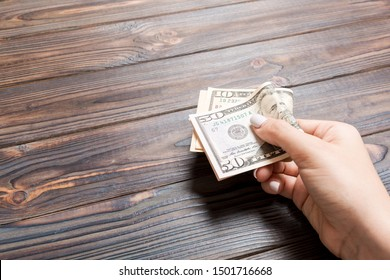 A pack of ten and fifty dollar bills in female hand on wooden background. Salary concept with copy space.