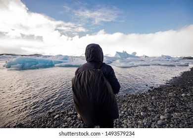 Pack your bags and get ready to travel the world! A guy standing with a bag pack admiring the nature in its purest form at Jökulsárlón glacial lake in Iceland with icebergs floating around.