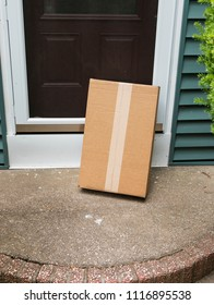 A package is delivered to a residential house and left out in the open which could lead to theft.