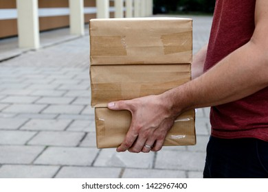 Package delivery. Delivery man is holding packaging or cardboard boxes. Delivery man at work.