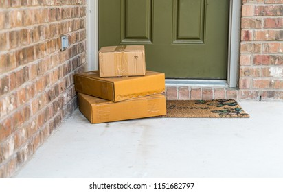 Package delivery on doorstep. Boxes and postal delivery on modern brick home doorstep on front green painted door