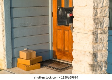 Package delivery , small boxes left on doorstep. Wooden door and brick column with three cardboard boxes sitting on doorstep