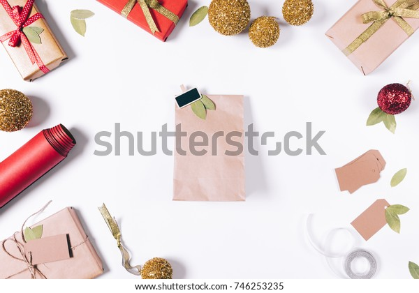 Package with a gift lying on the white table among Christmas decorations top view