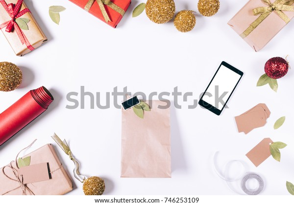 Package with a gift, mobile phone and Christmas decorations on a white table top view