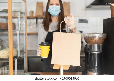 Package with a take away order and paper cup of coffee in hands of waitress, cafe owner, a woman in mask and gloves in out of focus. Protective measures due quarantine lockdown, pick up and go concept