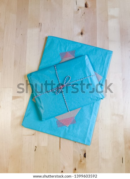 A package wrapped in blue paper and red and white twine sits on a wooden tabletop.