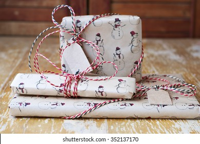 Packaged Christmas or New Year gift box with twisted striped red, black and white ribbon. Craft wrapping paper. Wooden shabby table. Wrapping paper with snowmen.