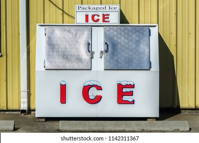 Packaged Ice freezer machine against a yellow wall during a hot and sunny day of summer outside a grocery store, Oregon, USA.