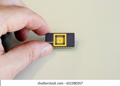 Packaged integrated circuit with visible die in human fingers for scale comparison on bright background