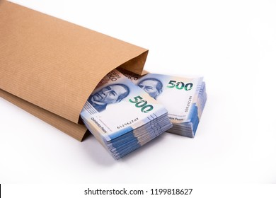 Packages of 500 Mexican pesos bills inside a paper bag, on a white background from above to the left
