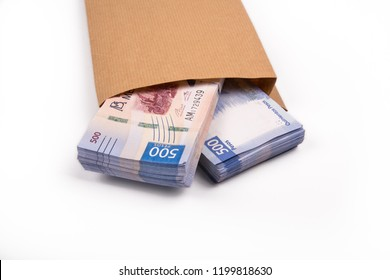 Packages of 500 Mexican pesos bills inside a paper bag, on white background from above