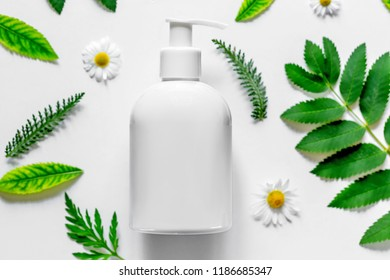 Packaging with cosmetic on white background with field flowers and leaves. The concept of summer and idea for advertisement of antiperspirant, deodorant. Flat lay.