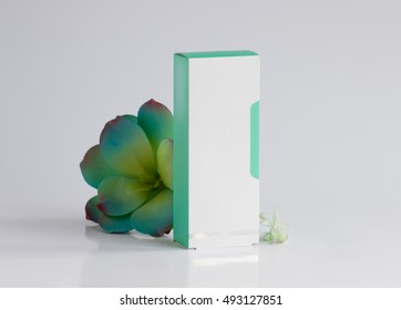 packaging for cosmetics white with green cardboard on a white background surrounded by a green flower, packaging for decorative cosmetics