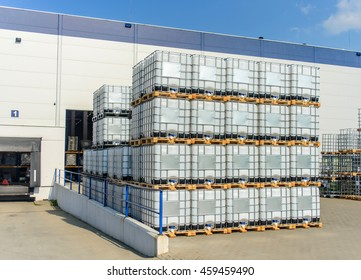 Packed pallets IBC conteiner of retail goods standing outdoors at a large modern warehouse in summer sun