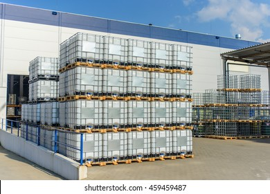 Packed pallets of retail goods standing outdoors at a large modern warehouse in summer sun