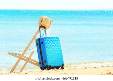 Packed suitcase, beach chair and hat at sea shore. Vacation concept
