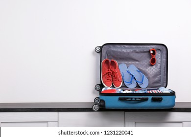 Packed suitcase with clothes and shoes on chest of drawers indoors. Space for text