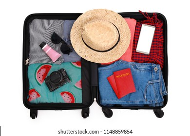 Packed suitcase or luggage with travel accessories on white background. Summer holidays, vacation and travel concept.
