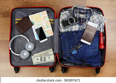 Packed suitcase with travel accessories on wooden background