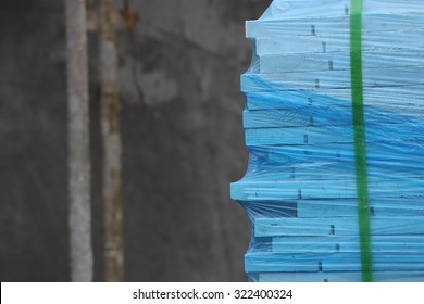 Packed Tiles. Stack of white wall covering tiles packed with blue transparent shrink wrap in a construction site.