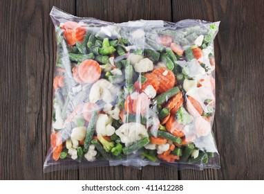 Packet of frozen vegetables on a old wooden table, top view
