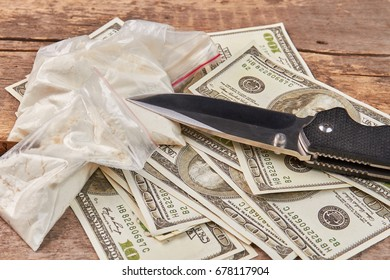 Packets with drugs, money, knife. Bags with cocaine, amount of dollars, knife close up. Use of narcotics is dangerous crime.