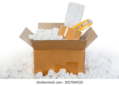 Packing accessories polystyrene plastic foam, parcel tape, cutter, plastic bubble shockproof wrap in parcel paper box for packing and shipping. Packing cardboard box and accessories concept.