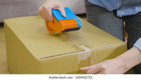 Packing carton boxes close up. focus on asian woman hands prepared cardboard container with help of adhesive tape on floor in living room. preparation move house relocation lifestyle concept.