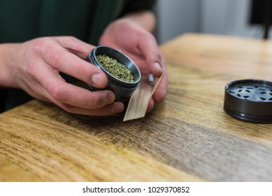 Packing a joint with ground up weed from a sleek metal grinder.