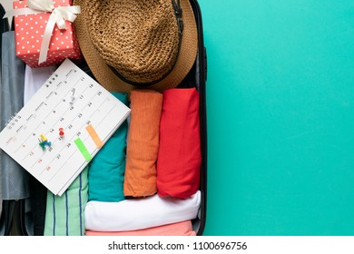 packing a luggage with calendar for a new journey and travel on green background