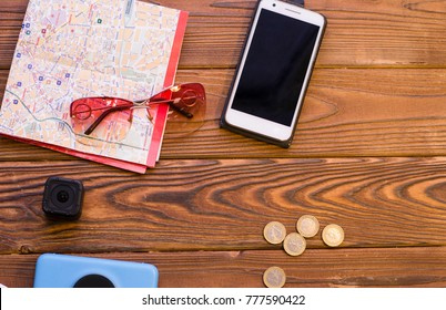 Packing luggage for a trip. A a folded map, a mobile phone, a photo camera, an action camera and coins on a rustic wooden background. Space for a text or product display, top view.