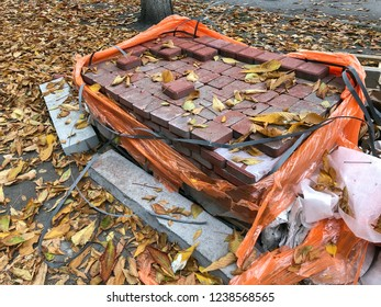 Packing of pink paving slabs in orange cellophane and plastic tape with lots of yellow autumn leaves. A pile of tiles for building. Building materials for the pedestrian walkway