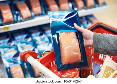 Packing of salmon fish in the hand of the buyer at the grocery store