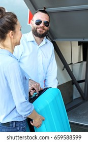 Packing suitcase for the bus. The driver helps the passenger put the suitcase in the trunk.