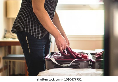 Packing suitcase in hotel room. Young man folding t-shirt on baggage in home bedroom. Open luggage on bed for vacation preparing. Person going on or leaving from holiday.