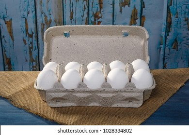 Packing of white eggs on blue, wooden background