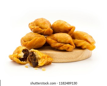 "Packshot close up view of ""Pan Klib"" traditional mini Thai puff dessert stuffed material with fish, curry, shallot, pepper seasoned sugar and salt on wood plate isolate on white background"