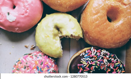 Pac-man cut donut among sprinkle donuts.