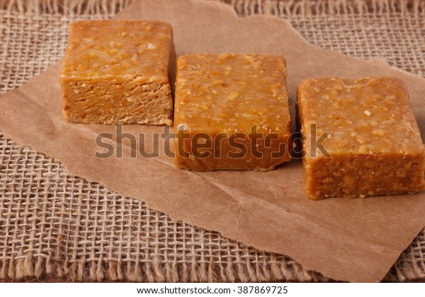 Pacoca - brazilian candy of ground peanut on wooden background. Selective focus