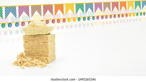 Pacoca, brazilian peanut candy with bran. Typical peanut candy from Festa Junina party. Festa Junina flags and a hillbilly hat. White background, space for text.