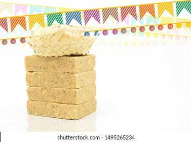Pacoca, brazilian peanut candy. Typical peanut candy from Festa Junina party. Festa Junina flags and a hillbilly hat. White background, space for text.