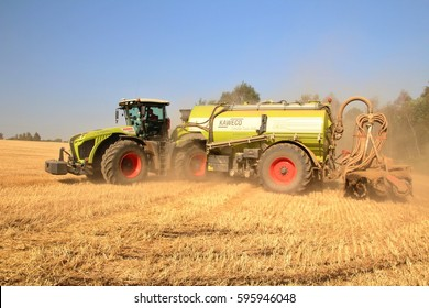 PACOV, CZECH REPUBLIC - August 15, 2015: Big tractor turning on headland, preparing soil for spring seeding of corn, field with wheat stubble, injecting slurry, dust in the air, side perspective